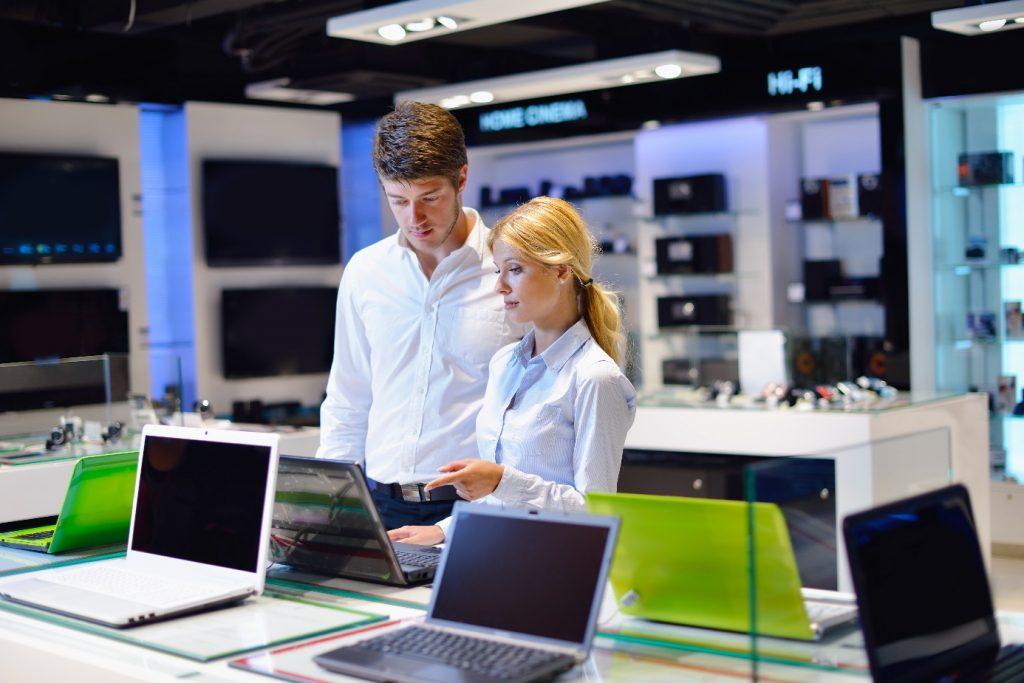 man op zoek naar laptop met verkoopster