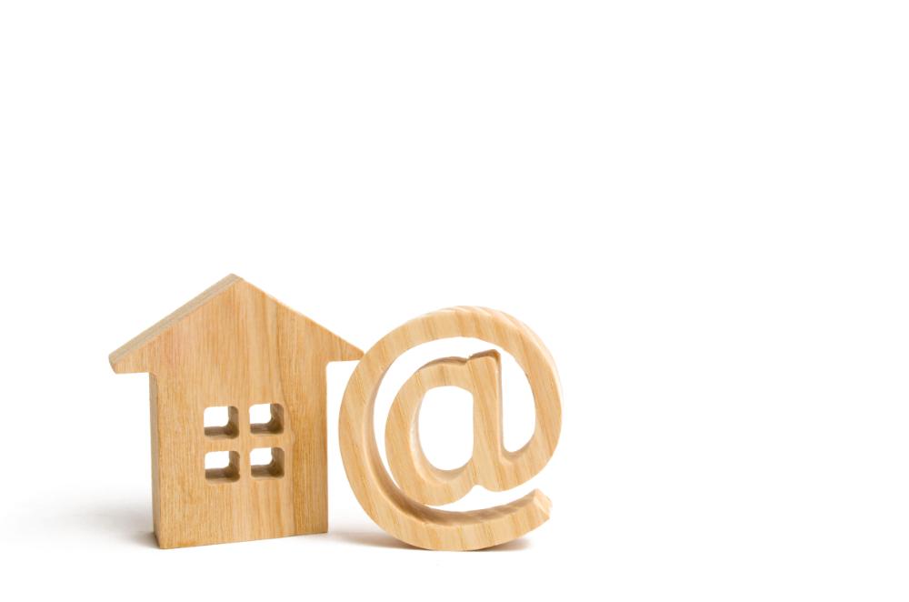 huis en @ -symbool uit hout gesneden