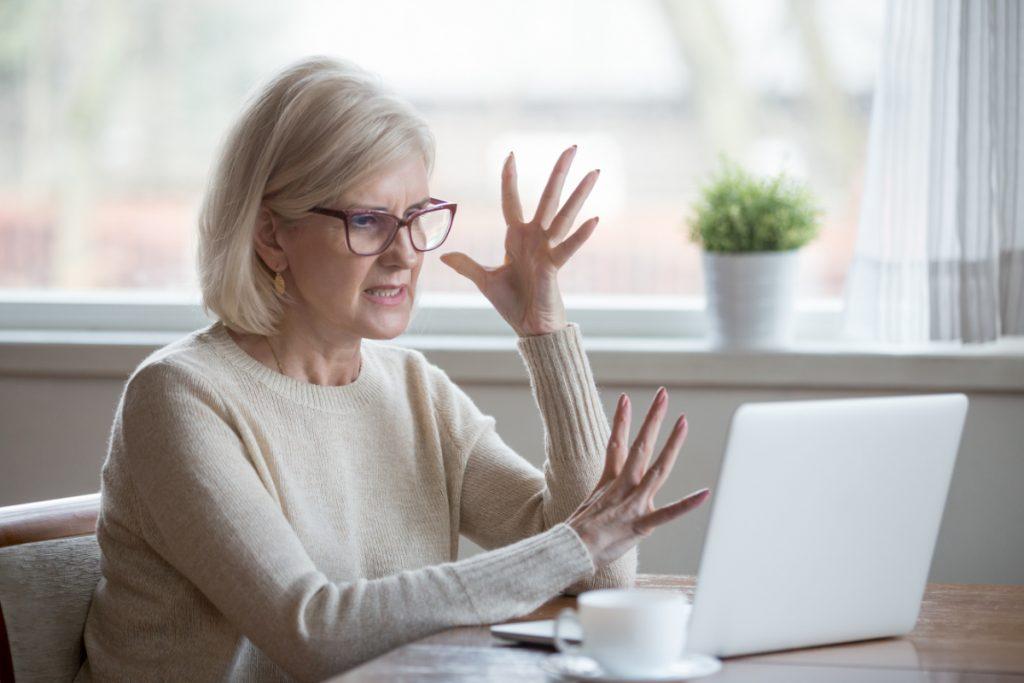 senior vrouw gefrustreerd met laptop