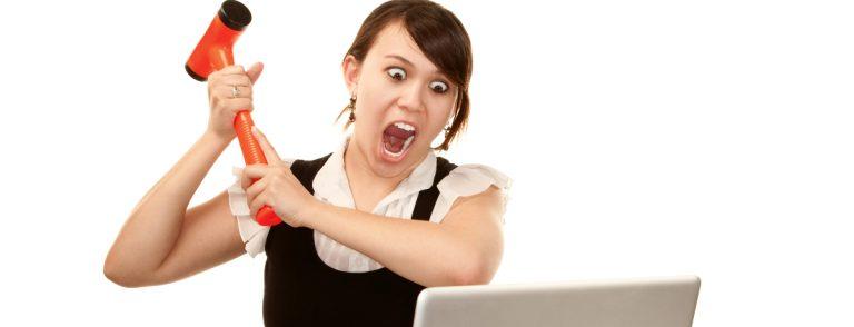Vrouw slaat laptop met hamer